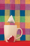 The tea bag hangs over a cup Stock Images