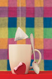 The tea bag hangs over a cup Stock Photos