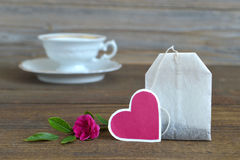 Tea bag with heart-shaped tag, porcelain tea cup and rose Royalty Free Stock Photos