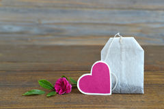 Tea bag with heart-shaped tag and rose Stock Photo