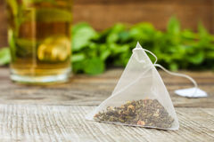 Tea bag, mint,  cup of tea. Tea bag on background of mint and and cup Royalty Free Stock Photos