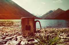 Tea bag in orange plastic Cup. Tea bag Cup on the background of the beautiful landscape and blue lakes. Tourist Hiking romance. Breakfast in the nature stock photo