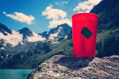 Tea bag in orange plastic Cup. On the background of the beautiful landscape mountains and blue lakes. Tourist Hiking romance. Breakfast in the nature royalty free stock image
