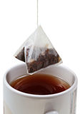 Tea bag over brewing tea in mug Stock Photo