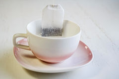 Tea bag put in white ceramic teacup. Closeup teabag put in white ceramic teacup on white saucer Stock Photos