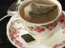 Tea bag steeping in a floral teacup. This shows a green tea bag steeping in a bone chine teacup with saucer and spoon. Cup has dainty pink, forget-me-knot type stock photo