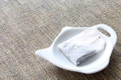 Tea-bag on a teapot shaped plate. Tea-bag on a teapot shaped white plate Royalty Free Stock Photo