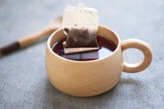 Tea bag in wooden cup Stock Image