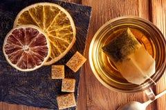 Tea bag on a wooden table, orange slices, sugar cubes Stock Images