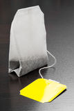 Tea bag with yellow label. On black background Royalty Free Stock Photography