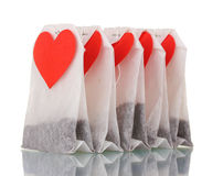 Tea bags with blank heart-shaped labels. Over the white royalty free stock photography