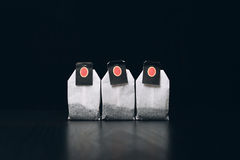 Tea bags on a dark background stand in a row Royalty Free Stock Photography