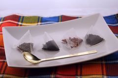 Tea bags. Four pyramid tea bags on a plate with a tea spoon Stock Images