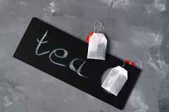 Tea on a gray background and a black sign and the inscription: Tea. Tea bags on a gray background and a black plate with the inscription: Tea stock photos