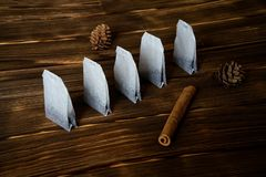 Tea bags lie on a wooden surface with cinnamon and pine cones stock photo