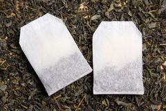 Tea bags over dried tea leaves background Stock Images