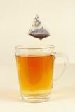 Tea bags over glass with brewed tea Stock Photos
