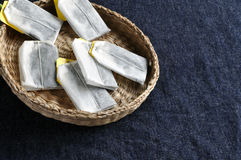 Tea bags in shallow basket. Tea bags rest in a shallow basket made of reed Royalty Free Stock Photography