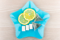 Tea bags, slices of lemon and lumpy sugar in plate Stock Photography