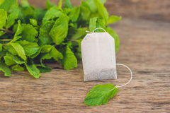 Tea bags on wooden background with fresh melissa, mint. Tea with mint concept royalty free stock photography