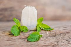 Tea bags on wooden background with fresh melissa, mint. Tea with mint concept.  royalty free stock photo