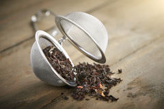 Tea ball with black tea and red fruit Royalty Free Stock Photography