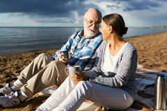 Tea on the beach. Affectionate senior couple having tea while relaxing on beach by water Royalty Free Stock Photo