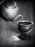 Tea being poured into a ceramic cup from a teapot. Stock Images