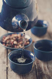 Tea being poured into cup. Toned photo Royalty Free Stock Image