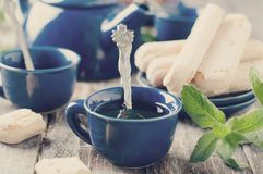 Tea being poured into cup. Toned photo Stock Photos