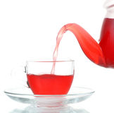 Tea being poured into glass tea cup isolated. On a white background stock photo