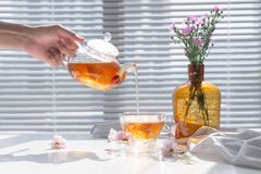Tea being poured into glass teacup in the morning. Stock Photos