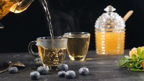 Tea being poured into glass transparent tea cup in slow motion. Cup of tea and teapot. Green Chinese Flower Tea Blooming. Blueberry, glass can with honey stock video footage