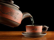 Tea being poured from kettle in cup Stock Image