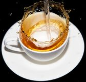 Tea being poured into a saucer with splashes on a black background Stock Photo