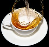 Tea being poured into a saucer with splashes on a black background Stock Images