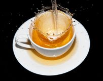 Tea being poured into a saucer with splashes on a black background Stock Photos