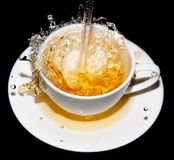 Tea being poured into a saucer with splashes on a black background Stock Photography