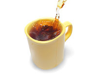 Tea being poured into tea cup  on a white Stock Photos