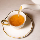 Tea being poured into tea cup, on white background. Royalty Free Stock Image