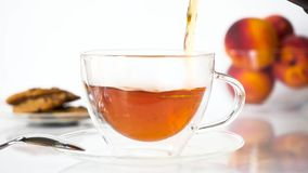 Tea Being Poured into Transparent Cup in Slow Motion. Tea being poured into transparent cup on a plate with a metal spoon on a white table. Peaches and cookies stock footage