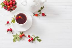 Tea with berries of a dogrose on a wooden background stock photography