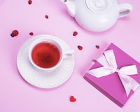 Tea from berries of viburnum in a white ceramic mug. And box with a gift on a pink background Royalty Free Stock Photo