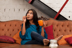Tea and biscuit. Girl on sofa with tea and biscuit royalty free stock image