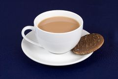 Tea and biscuit. A cup of tea with a chocolate biscuit in the saucer Stock Photo