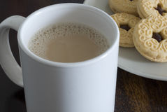 Tea and biscuits. A mug of white tea and plate jam biscuits Royalty Free Stock Photography