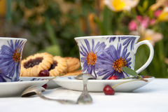 Tea and biscuits on the table. Cups of tea and biscuits on the table in the garden. closeup. green background Royalty Free Stock Images