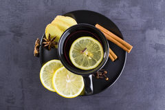 Tea in black cup with spices. Ginger, lemon, anise, cloves Royalty Free Stock Images