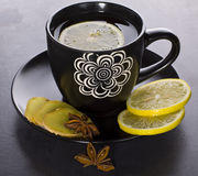 Tea in black cup with spices. Ginger, lemon, anise, cloves Stock Photo