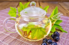 Tea with black currants in glass teapot on board Stock Photography